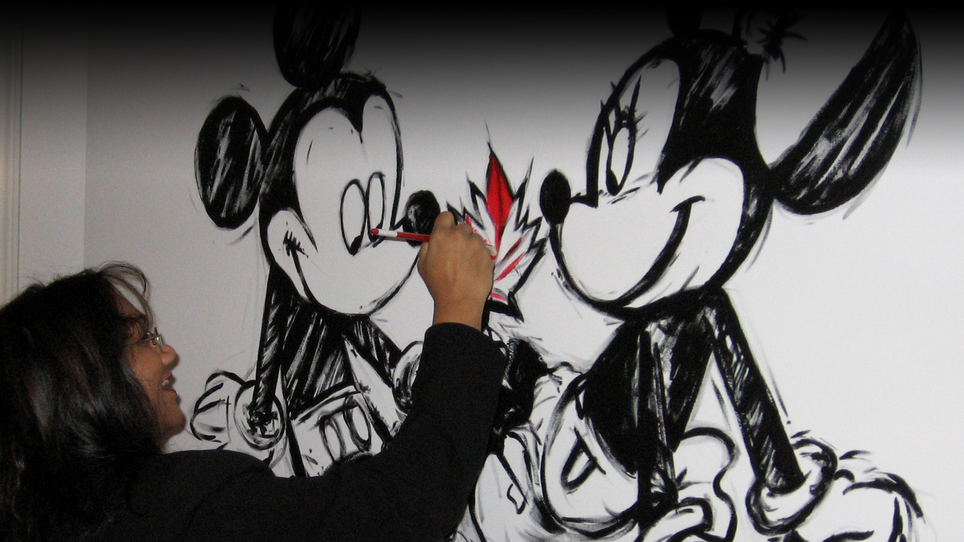 A woman painting a red leaf on a wall image of Mickey and Minnie Mouse.