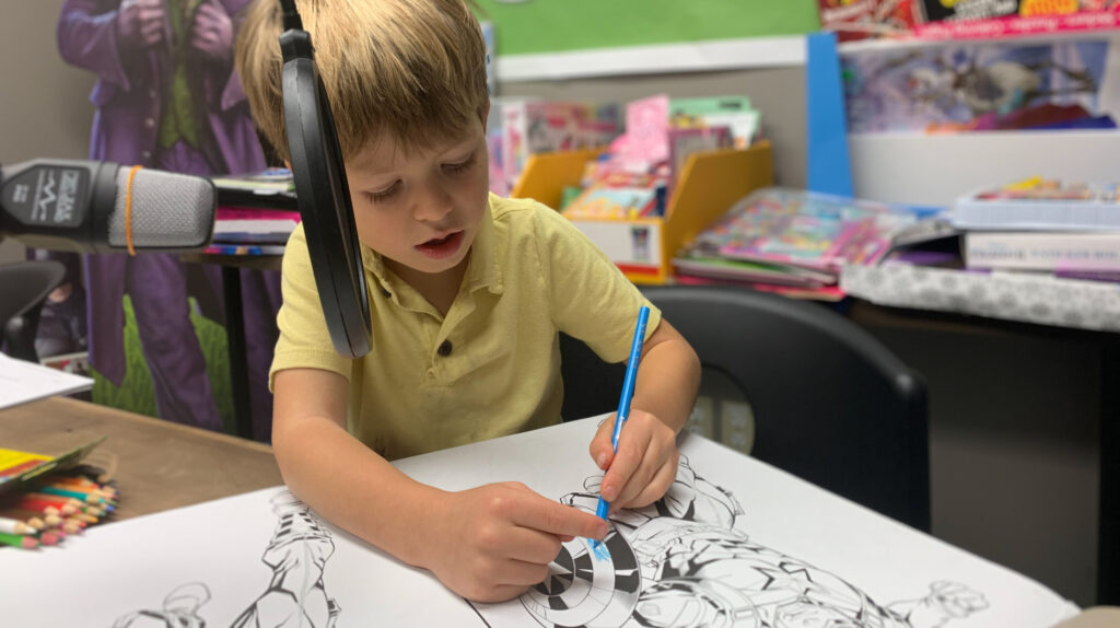 Young small child colouring a picture of Captain America in the greenre studio.