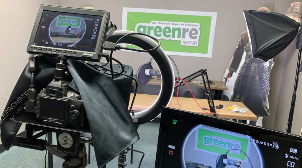 A view from behind a large video camera, pointed towards an empty table and the greenre logo on the wall.